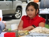 A young girl helps serve food