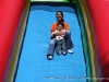 Mom laughs as she comes down the slide with her son