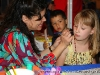 A young girl gets her face painted as a boy looks on
