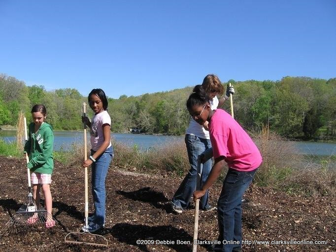 Tatyana Finks, Jennifer Murray, and Caitlin Williams of girl scout troop 2559 spreading mulch in 2009