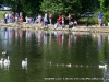Parents and their children line the shore at the Fairgrounds Pond
