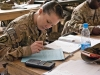 Spc. Amber Eddy, Headquarters and Headquarters company, 5th Battalion, 158th Aviation, aviation operations specialist, a native of Brigham, Utah takes notes and attempts to solve a problem posed to the the students during a class covering probability and statistics in a TF Ready classroom in Balkh Province, Afghanistan Nov. 14. U.S. Army photo by Sgt. Duncan Brennan, 101st CAB public affairs