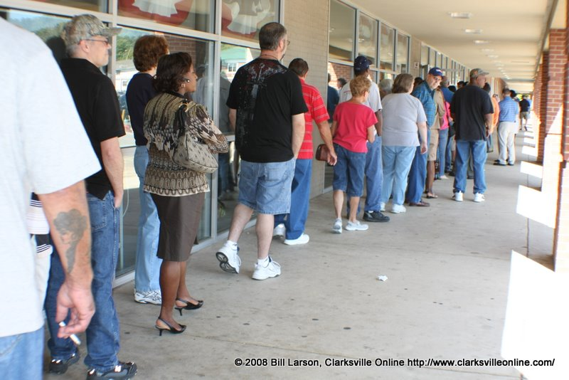 Approximately 100 people stand in line waiting to vote.
