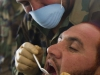 A medic with the ANA's 2nd Commando Khandak, 203rd Corps, uses a dental mirror while performing an oral exam on a fellow Commando, during a basic dental class on at forward operating base Thunder, Afghanistan, July 21. (U.S. Army photo by Sgt. Justin A. Moeller, 4th Brigade Combat Team Public Affairs)