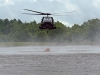 A UH-60M Black Hawk helicopter with A Company, 6th Battalion, 101st Combat Aviation Brigade, 101st Airborne Division (Air Assault)  scoops up water into a bucket slung from the helicopter during wildfire operations training at Fort Campbell, Ky., August 19, 2013. (U.S. Army photo by Sgt. Duncan Brennan, 101st CAB Public Affairs)