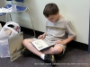 Not waiting to get home, this young man sat down in the floor and began reading one of this new books.