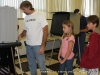 Troy Bellar votes as Zac (age 10), and Paige (age 8) look on.