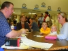 A voter resolves a problem with the Special Clerk at Glenellen Elementary School, as her children look on.