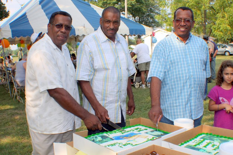Gene, Orville and Milan Lewis prepare to slice retirement celebration cake