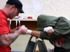 A trainer tapes a fighter hands as he mentally prepares himself for fight