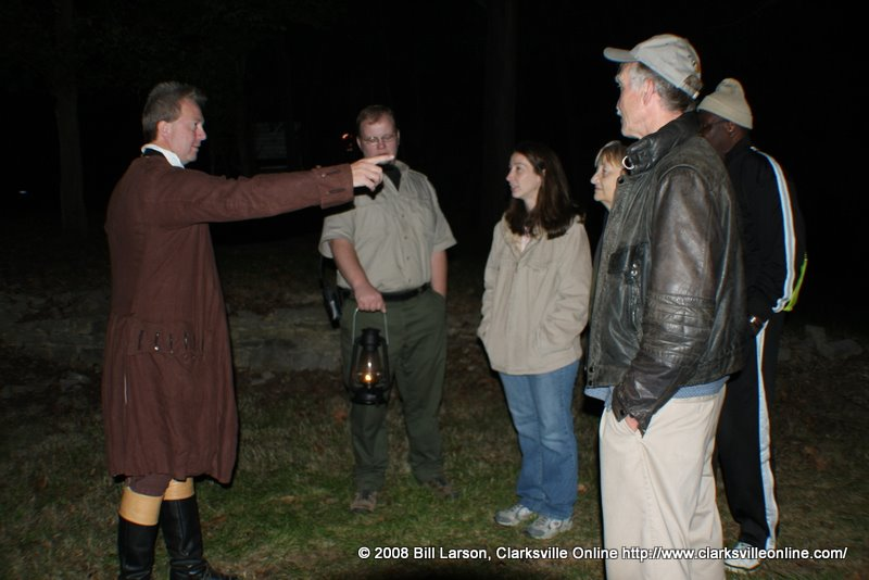 A tour listens to one of the re-enactors tell his tale