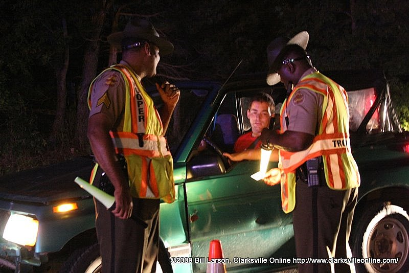THP Trooper Curley Jackson checks a drivers license as SGT Hobbs looks on