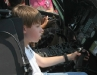 A child sits behind the controls of a helicopter