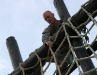 1st Lt. Joey Keller prepares to climb down the cargo net as part of the as part of the tough one obstacle at the Toughest Air Assault Soldier Competition