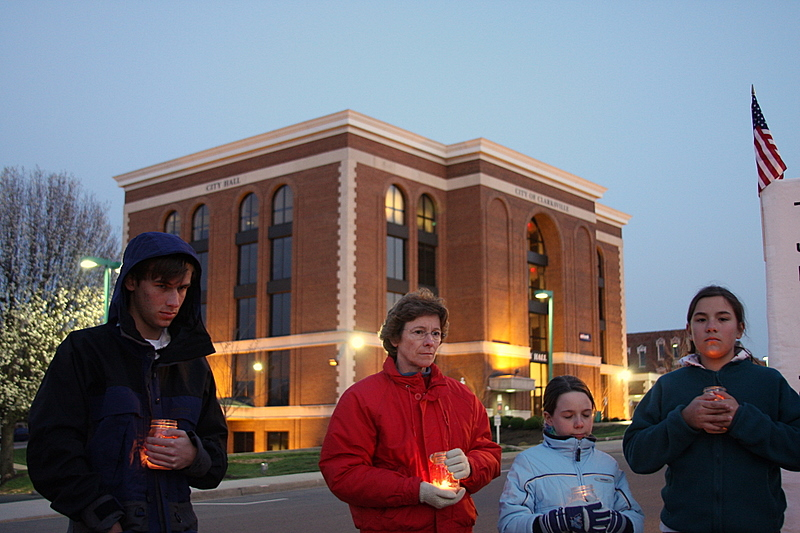 """Vigil members stand in front of City Hall which lit the """"Eternal"""" flame to mark the 4000th US death in Iraq"""