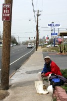 A man waits for the bus while looking for a job