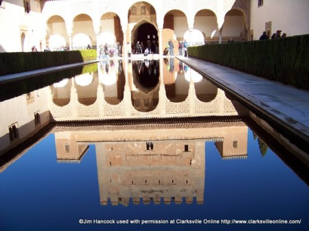 A reflecting pool with the Alhambra in the background in Granada, Spain.