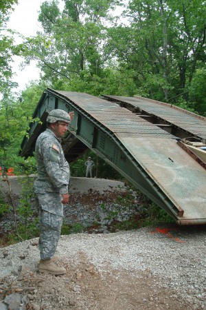 Sgt. Terry Bell, 190th Engineer Company, 230th Engineer Battalion, 194th Engineer Brigade, guides a Armored Vehicle Launched Bridge into place across a creek at the Killebrew detour off Angels Road at Fort Campbell today.