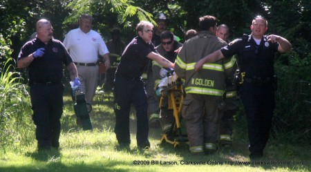 Clarksville, TN - Emergency Responders rush the victim out of the woods