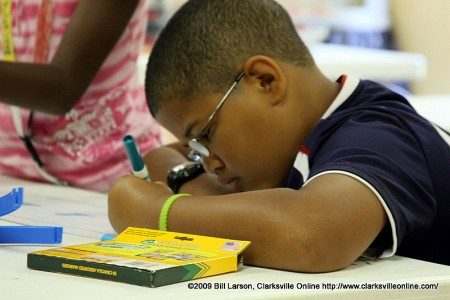 A young man colors while participating in the City of Clarksville's Summer youth program