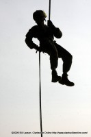 A soldier silhouetted against the sky repels down from the top of the tower at the Toughest Air Assault Soldier Competition