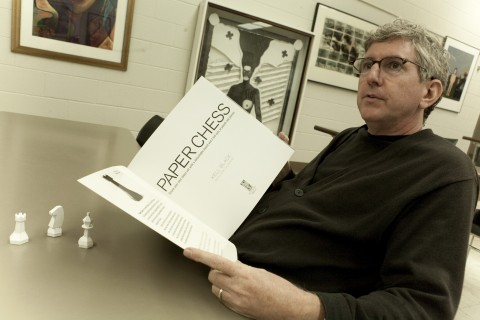 "Kell Black, APSU professor of art, looks over a copy of his new book, ""Paper Chess."" In front of him are a few chess pieces he designed for the book. (Photo By Rollow Welch/APSU Public Relations and Marketing)"