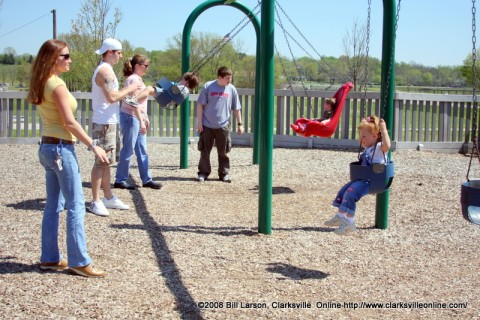 Parents pushing their children on the swings at one of Clarksville TN's may Parks