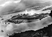A photograph taken from a Japanese aircraft of the attack on Pearl Harbor. The photo shows Battleship Row as a torpedo impacts the USS West Virginia