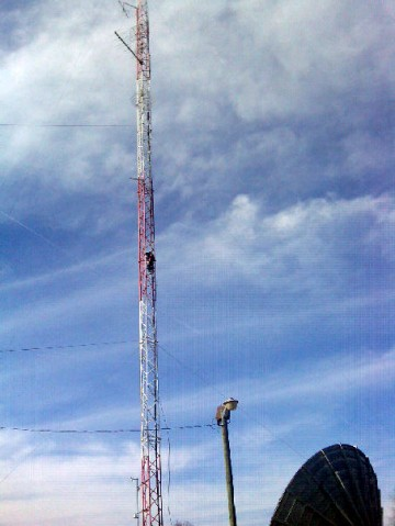 A Charter Technican climbs the antenna tower to install the antenna for the WKAG signal test