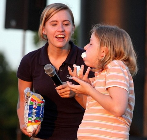 A marshmellow drops out of a young girls mouth knocking her out of the chubby bunny contest.