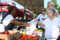 Deanna (left) serves several customers at the Montgomery County Farmers Market on Thursday