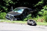 A single wheel from the pickup truck sits beside the road with the rest of the vehicle resting off the side of the road