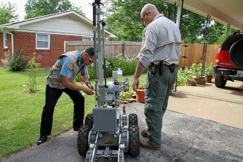 Bomb Squad techs with the robot after the discharge of the water cannon.