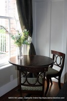 A simple table with flowers bathes in the morning light through a generous window on the south side of the house
