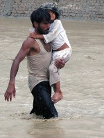 An Afghan man carries a young child to safety during encroaching flood waters in Nari Shahi village, Beshood District of eastern Afghanistan's Nangarhar province July 28th. (U.S. Army courtesy photo)