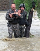U.S. Army Sgt. Robert Huff, of Erlanger, KY, and U.S. Army Cpl. Patrick O' Rourke, Front Royal, VA, rescue an Afghan child from encroaching flood waters in the Nari Shahi village in the Beshood District of eastern Afghanistan's Nangarhar province July 28th. (U.S. Army courtesy photo)
