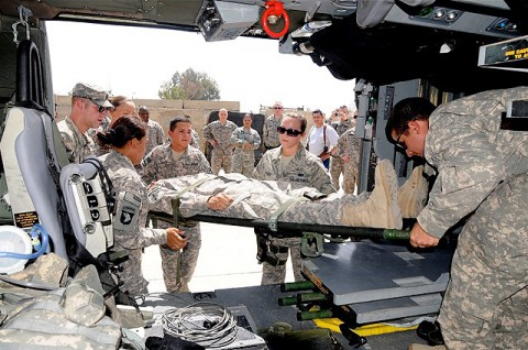"""Students in a recent litter-bearer class held at Salerno Hospital get some hands-on training by loading a """"patient"""" into an awaiting Blackhawk helicopter.  (Photo by U.S. Army Sgt. Brent C. Powell, 3rd Brigade, 101st Airborne Division)"""