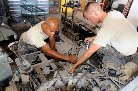 U.S. Army Spc. Luis A. Pagan (left), from Hoboken, NJ, wheeled vehicle mechanic, maintenance platoon, Company G, 626th Brigade Support Battalion, 3rd Brigade, 101st Airborne Division, and U.S. Army Sgt. Phillip T. Brown, from Pensacola, FL, a wheeled vehicle mechanic and shop foreman for the maintenance platoon, Co. G, 626th BSB, 3rd Bde., 101st Airborne Div., work together to remove parts from a humvee engine in the unit's maintenance shop. (Photo by Sgt. Brent C. Powell, 3rd Brigade, 101st Airborne Division)