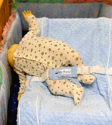INCORRECT USE: Photo of re-enactment of doll falling over side of Nap Nanny® placed in crib.
