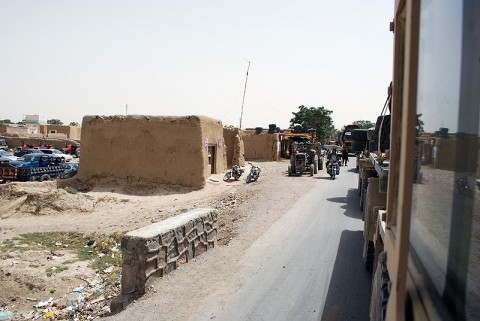 Task Force Iron Soldiers drive through an Afghan village during a recent convoy of vehicles and equipment.  The convoy was the largest resupply the unit has conducted since arriving in February.  Despite encountering five IEDs and being fired upon by insurgents, the mission was a success and no injuries were sustained. (Official U.S. Army Photo)