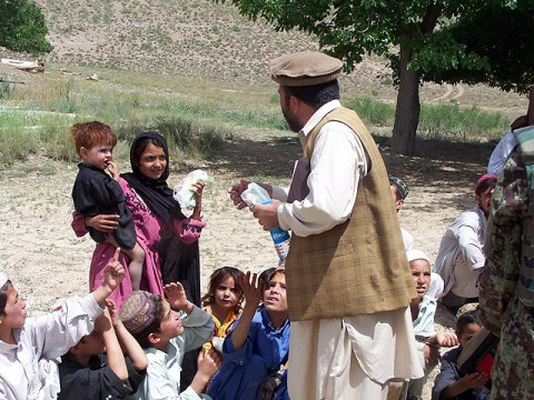 Dawlet Khan, Bermel District sub governor, hands out various items to the children in Faqiran Village after a Shura he held on the spot July 5.  Afghan National Security Forces and Rakkasan Soldiers provided security for the Shura. (U.S. Army Courtesy Photo)