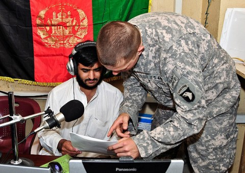 """Abdulsalam Omary, """"Voice of the Pech"""" broadcasting manager, reviews a press release with U.S. Army 1st Lt. Aaron Barker of Key West, FL, from Task Force Bulldog's fires and effects coordination cell, before going on the air July 19th.(Photo by U.S. Army Capt. Jonathan J. Springer, 1st Battalion, 327th Infantry Regiment)"""
