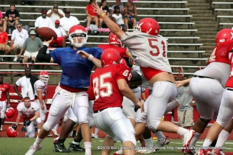 The red shirt QB lobs a pass in the face of a stiff defense.