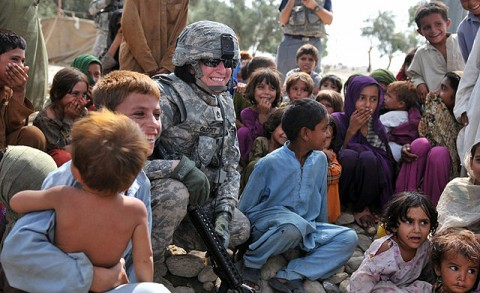 U.S. Army Staff Sgt. Nicole Olcott, poses with children after she donated two boxes of school supplies to them Aug. 14th. The children were living in an internally displaced persons camp in the Beshood District of eastern Afghanistan's Nangarhar province. Olcott received donations from the Matthew Freeman Foundation, the Adopt-A-Soldier program and her own nonprofit foundation, Operation New Start. (Photo by U.S. Army Spc. Albert L. Kelley, 300th Mobile Public Affairs Detachment)