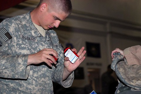 U.S. Army Pfc. Peter Lessard, 342nd Military Police Company customs agent and Concord, NH, native, inspects the contents of a redeploying Airman's baggage at the Bagram Airfield's customs terminal August 2nd. Every bag is thoroughly inspected for unauthorized items before it is allowed to leave Afghanistan. (Photo by U.S. Army Spc. Jay Venturini, 304th Public Affairs Detachment)