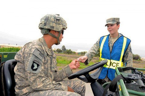 U.S. Air Force Staff Sgt. Amber R. Perez (right), a native of Vancouver, WA, and a security forces patrolman with the 655th Air Expeditionary Squadron, gives an identification card back to a Task Force Rakkasan Soldier on Camp Salerno during a recent vehicle safety enforcement  checkpoint.  (Photo by U.S. Army Sgt. Brent C. Powell, 3rd Brigade, 101st Airborne Division)