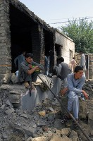 Children sit on the rubble outside the kitchen of the old Asadabad orphanage. The new orphanage will include 10 classrooms, four other rooms for teachers, and a dining hall.  (Photo by U.S. Air Force 1st Lt. Amy Abbott Kunar Provincial Reconstruction Team Public Affairs)