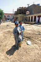 "A child wearing a ""Support the Troops"" hat wanders through the empty lot where the new Asadabad orphanage will be built. (Photo by U.S. Air Force 1st Lt. Amy Abbott, Kunar Provincial Reconstruction Team)"
