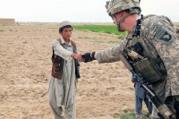 U.S. Army 1st Lt. Vance Gonzales, a native of Weddinton, NC, and executive officer, Company A, 3rd Battalion, 187th Infantry Regiment, 101st Airborne Division out of Fort Campbell, KY, takes a moment to shake hands with a young Afghan boy from the Sardar Kala Village of the Andar District in Ghazni Province August 6th. (Photo by U.S. Army Spc. Lorenzo D. Ware, 982nd Combat Camera Company)