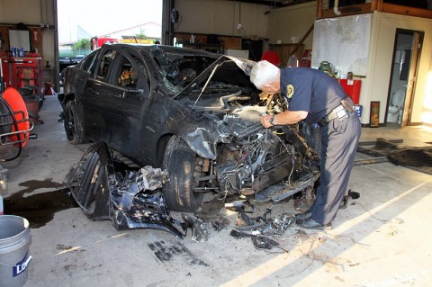Photo-Officer Bechtold inspecting Amy Fetter's burned vehicle.